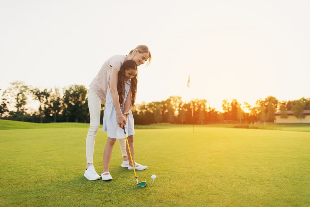 A Woman Is Teaching A Girl To Play Golf