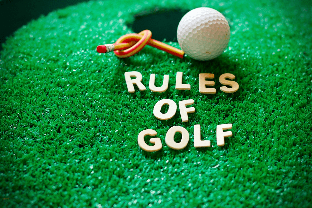 Rules of golf on green grass with golf ball